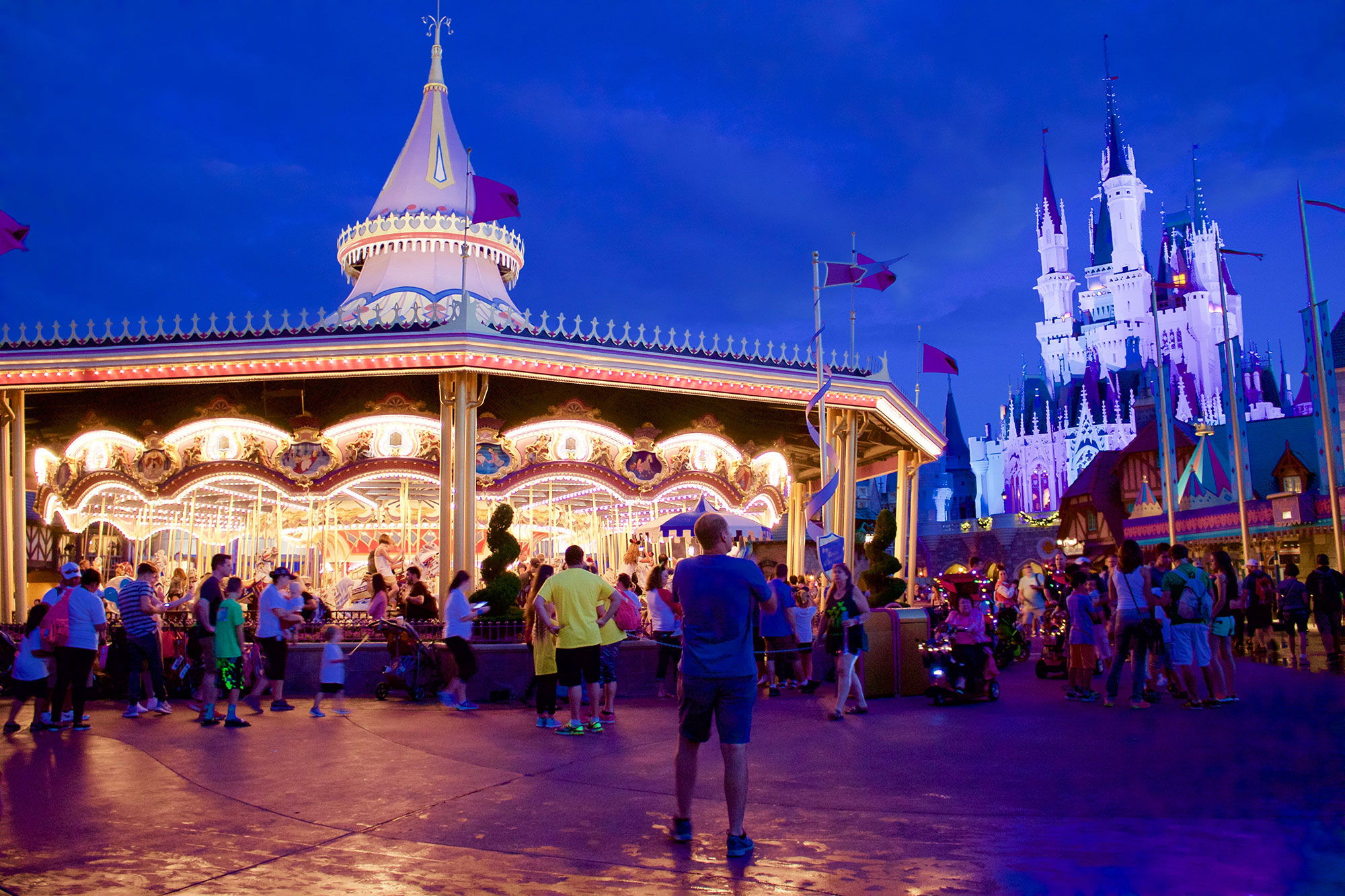 Prince Charming Regal Carrousel lights up the night behind Cinderella's Castle.